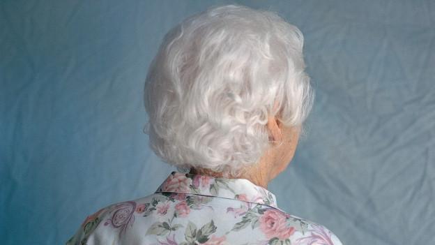 Eine weisshaarige Alzheimer-Patientin mit geblümter Bluse steht mit dem Rücken zur Kamera