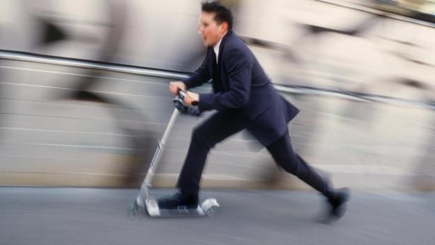 Das Bild zeigt einen jungen Mann, welcher mit einem Micro Scooter im Zürcher Verkehr unterwegs ist.