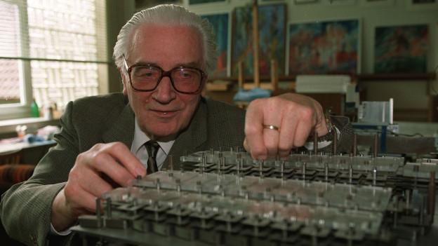 Konrad Zuse in den 80er-Jahren mit einem nachgebauten Modell seines Computers.