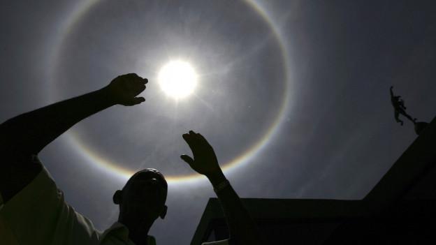 Zu sehen ist ein farbiger Ring um die Sonne. Davor steht ein Mann mit ausgebreiteten Armen.