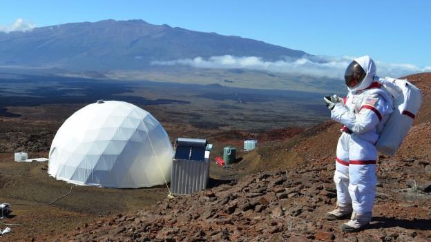 Forscherin Christiane Heinicke geht in einem Astronautenanzug über Fels.