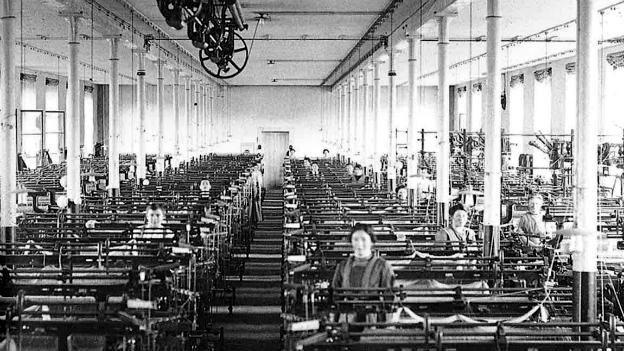Wenige Frauen, die in Fabrikhalle an Webmaschinen sitzen.