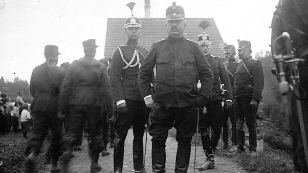 Im Vordergrund Ulrich Wille, der, umgeben von Offizieren direkt in die Kamera blickt. Alle in Uniform.
