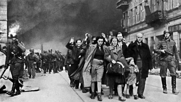 Das zwischen April und Mai 1943 aufgenommene Foto zeigt eine Gruppe polnischer Juden, die nach dem gescheiterten Aufstand von Soldaten der SS aus dem brennenden Warschauer Ghetto zur Deportation abgeführt wird.