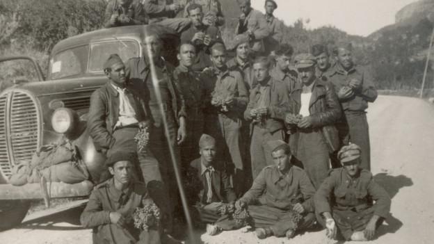 Rund ein Dutzend junge Männer in Uniform vor einem Auto.