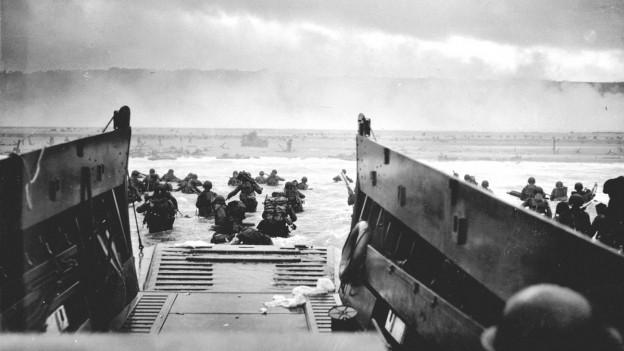Das Bild zeigt den Blick aus einem Landungsboot heraus. Soldaten waten an Land, über der Küste steigt Rauch auf.