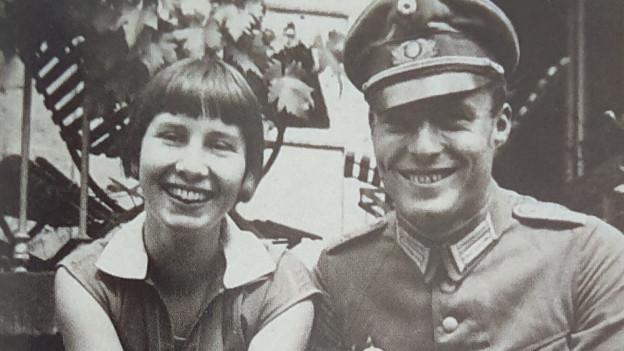 Vor ihrem Haus sitzt das Ehepaar Stauffenberg, lachend, eng aneinander geschmiegt.