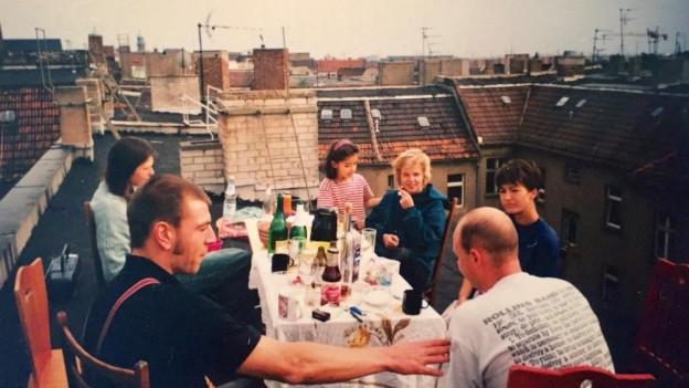Eine Gruppe sitzt auf einem Dach in Berlin und isst.