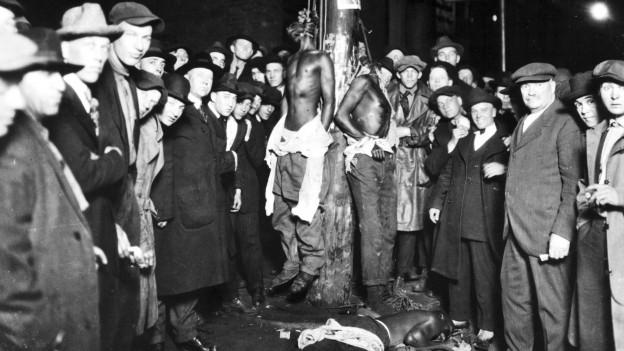 Postkarte von 1920, die die gelynchten schwarzen Männer an der Strassenlaterne zeigen. Umgeben von lachenden Weissen.