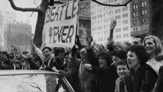 """Fans warten am Strassenrand auf die Beatles - ein Transparent mit der Aufschrift """"Beatles 4ever"""" wird hochgehalten."""