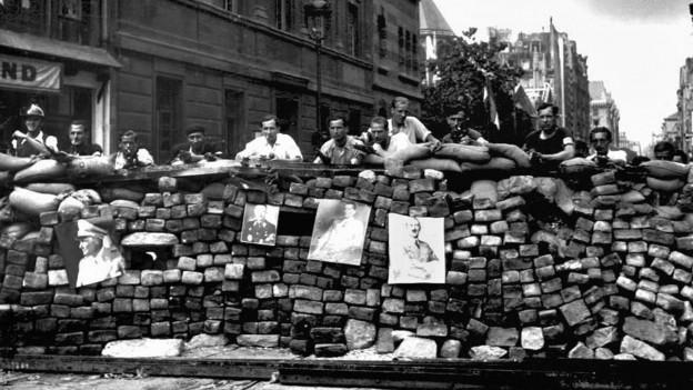 Aufnahme von Résistance-Kämpfern, die hinter einem Steinwall stehen.