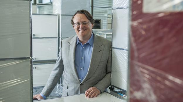 Alexander Schärer, Geschäftsführer von USM, umgeben von verpackten USM Büromöbeln