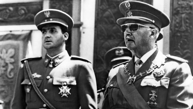 Ein greiser Francisco Franco mit dem späteren König Juan Carlos. Beide sind in Uniform.