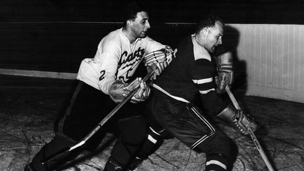 Der Schweizer Eishockeyspieler Elvin Friedrich (rechts) setzt sich in einem Trainingsspiel gegen die Canadian Flyers gegen den Kanadier Davito durch. Die Schweiz gewinnt das Spiel mit 7:2. Die undatierte Aufnahme stammt aus den 1960er Jahren.