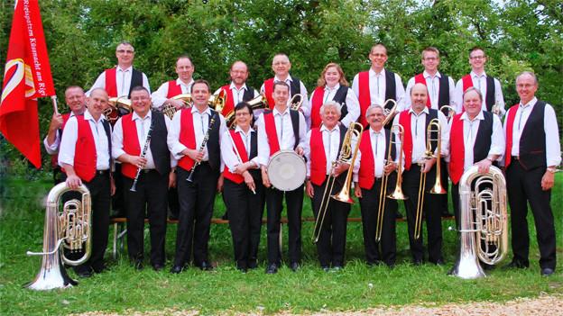 Gruppenbild mit Musikantinnen und Musikanten in rot-weiss-schwarzen Uniformen.