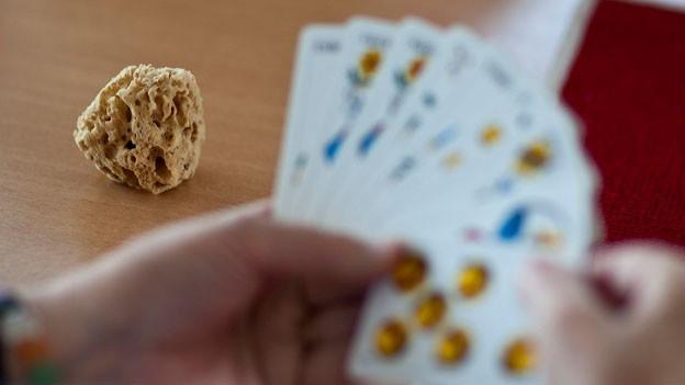 Gefächerte Jasskarten in einer Hand.