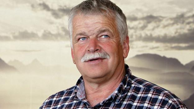 Der grauhaarige Alois Holdener mit Schnurrbart vor einem Bild mit Berglandschaft.
