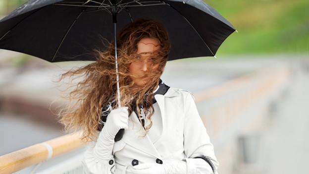 Eine junge Frau mit Regenschirm und vom Wind verwehten Haaren im Gesicht.