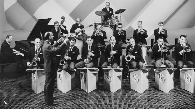 Schwarz-Weiss-Fotografie mit Orchester und Dirigent.