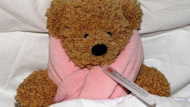 Teddybär mit rosa Schleife und Fieberthermometer