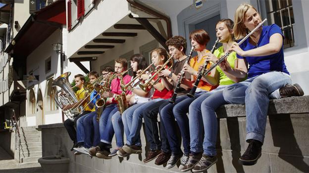 Junge Blasmusikanten sitzen auf einer Mauer und musizieren.