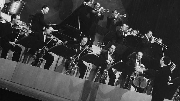 Ein Orchester spielt unter der Leitung von Cedric Dumont.