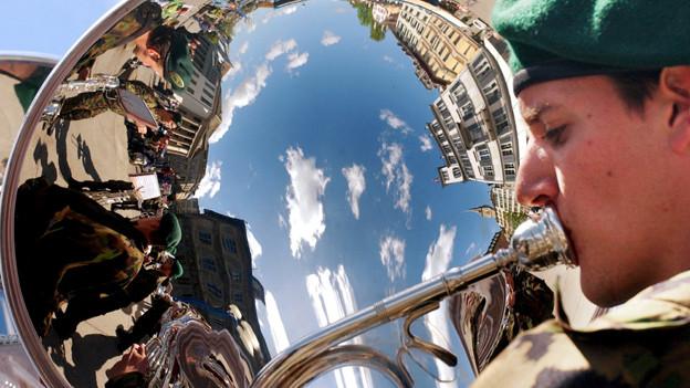 Der blaue Himmel und Haeuser am Zuercher Limmatquai spiegeln sich am Samstag, 3. Mai 2003, in der Posaune eines Musikers vom Rekrutenspiel 7/03 Herisau-Schönengrund.