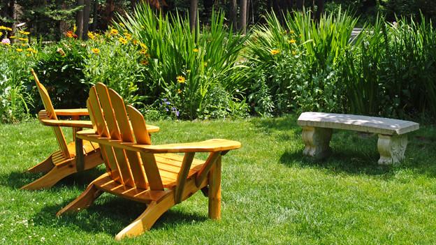 Zwei Holzstühle in einem Garten und ein Steinbank.