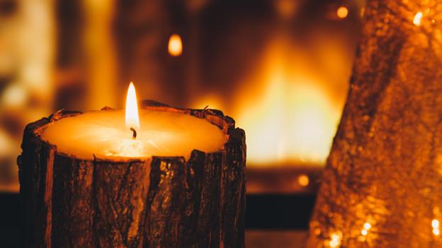 Eine brennende Kerze in einer Baumrinde.