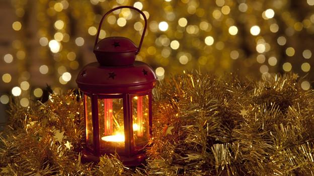 In einer roten Laterne brennt ein Teelicht. Die Laterne steht auf goldfarbenem Lametta.