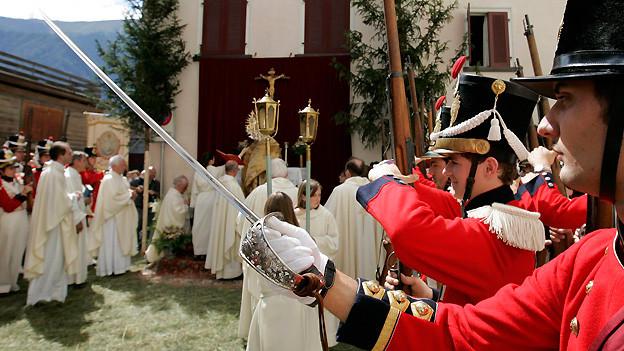 Mitglieder der Knabenschaften in farbenprächtigen Uniformen begleiten im Juni 2007 die Fronleichnams-Prozession durch die Gassen von Domat/Ems.
