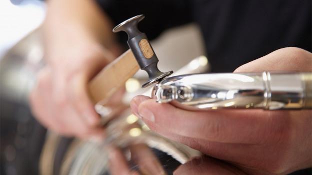 Ein Blasinstrumenten-Reparateur bei der Arbeit.
