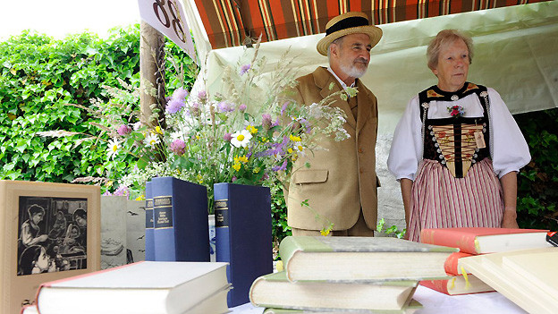 2010 am Gotthelf-Märit in Sumiswald: Besucher in Kleidung aus Gotthelfs Zeiten am Stand mit Büchern von Jeremias Gotthelf.