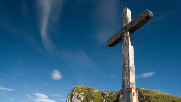 Dient häufig als Symbol für Jodlermessen: ein Kreuz auf einem Berggipfel.