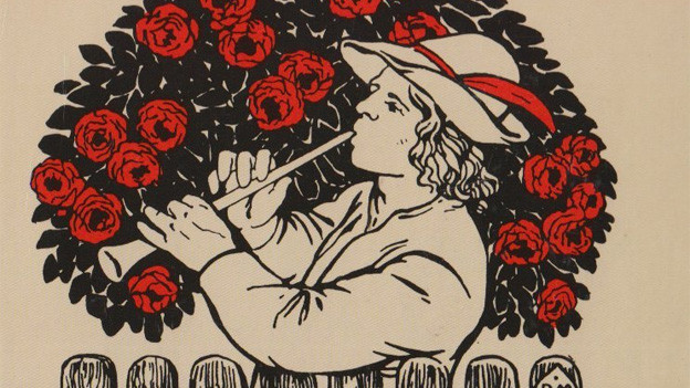Ein junge Mann mit Hirtenhut steht vor einem Rosenbusch und spielt Flöte.