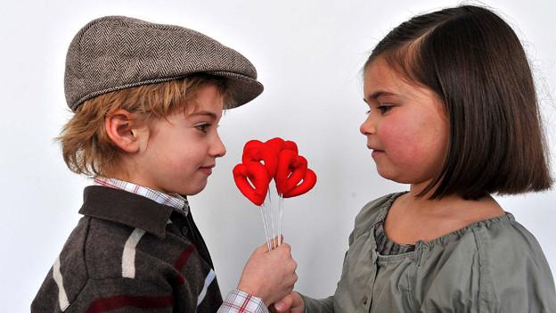 Mädchen und Junge überreichen sich Strauss an Bonbon-Herzen.