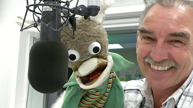 Die Handpuppe und der Komiker vor dem Mikrofon im Radiostudio.