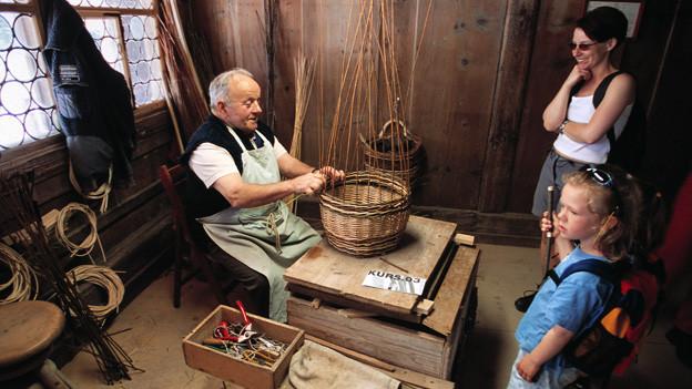 Im Freilichtmuseum Ballenberg wird bis heute traditionelles Handwerk demonstriert. In der Aufnahme von 2003 schauen zwei Gäste einem Korbflechter bei seiner Tätigkeit zu.
