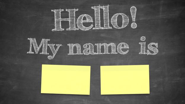 «Hello! Ma name is» steht mit Kreide auf einer Wandtafel geschrieben.
