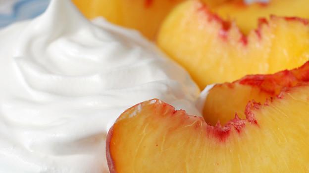 Lecker: Pfirsichschnitze, serviert mit einem Löffel geschlagenen Rahms.