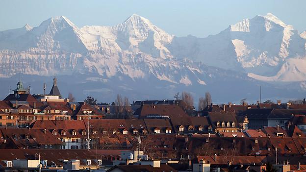 Eiger, Mönch und Jungfrau hinter den Dächern der Stadt Bern.