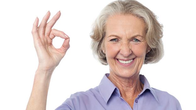 Seniorin macht Handzeichen.