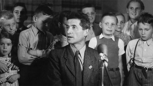 Carl Stemmler 1951 mit Buben und Mädchen während der Sendung «Kind und Tier»
