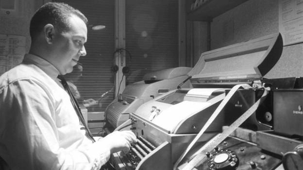 Historische Aufnahme von einem Mann vor einer Telex-Maschine.
