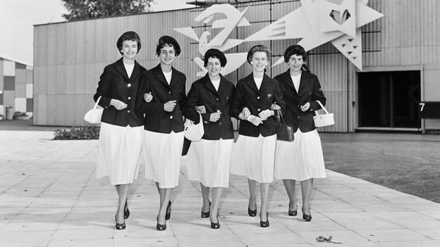 Fünf Hostessen posieren vor dem Wandbild mit dem Titel «Die Frau im Dienste des Volkes» an der SAFFA 1958 auf der Landiwiese in Zürich.