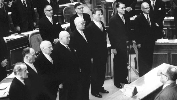 Die Vereidigung des Gesamtbundesrates vor der Vereinigten Bundesversammlung am 17. Dezember 1959. Von links nach rechts: Max Petitpierre (FDP), Paul Chaudet (FDP), Friedrich Traugott Wahlen (BEB), Jean Bourgknecht (CVP), Willy Spühler (SP), Ludwig von Moos (CVP), Hans-Peter Tschudi (SP) und Bundeskanzler Charles Oser.