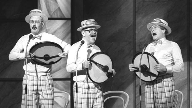 Schwarz-Weiss Fotografie mit den drei Kabarettisten, die mit Strohhüten auf der Bühne singen.