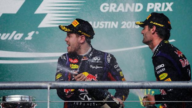 Sebastian Vettel (links) feiert am 17. November 2013 seinen Grandprix-Sieg in Austin, Texas mit einer Champagner-Dusche. Sein Teamkollege Mark Webber feiert als Drittplatzierter mit.