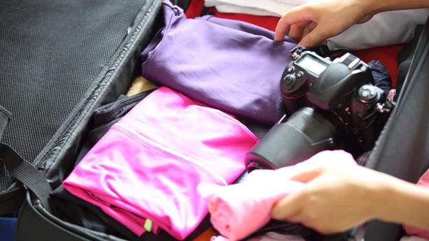 Ein offener Koffer mit Kleidungsstücken und einem Fotoapparat.