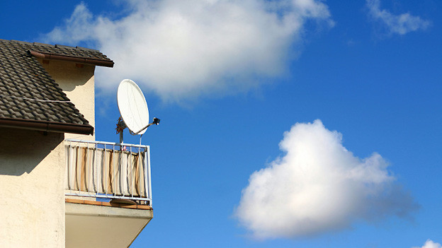 Eine auf einem Eckbalkon montierte Satellitenschüssel.